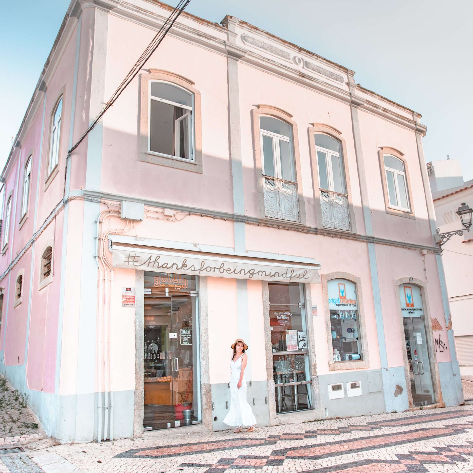 Standing in front of a beautiful pink cafe in Lagos, Portugal