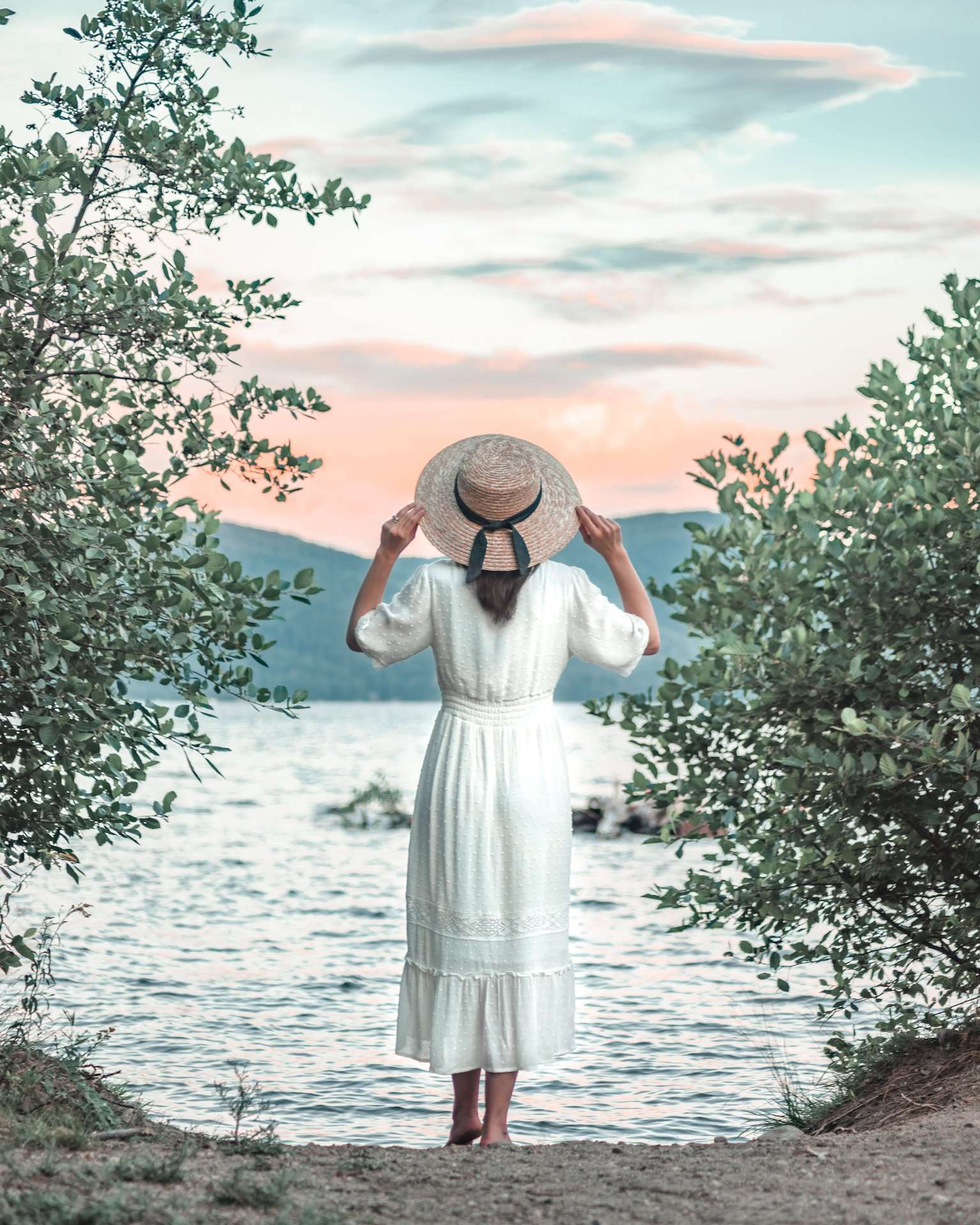 woman wearing sunhat and watching sunset