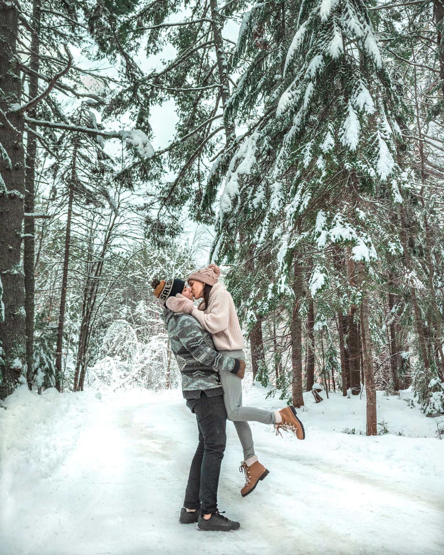 couple kissing in snowy woods