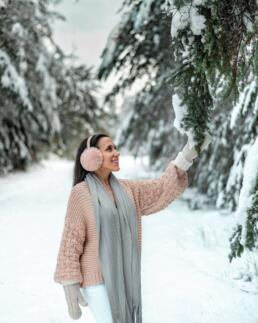 girl admiring snow-covered tree branch