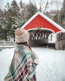 girl and red covered bridge with snow