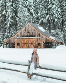 girl at snow covered cabin in the woods