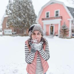 girl blowing snow in front of pink house