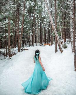 girl in blue dress in snowy forest