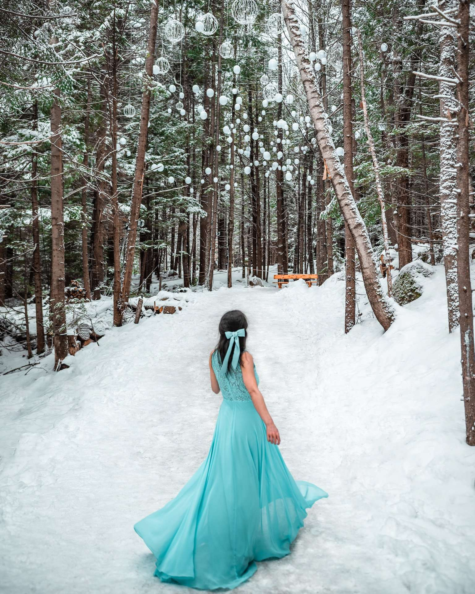 girl in blue dress in snowy forest