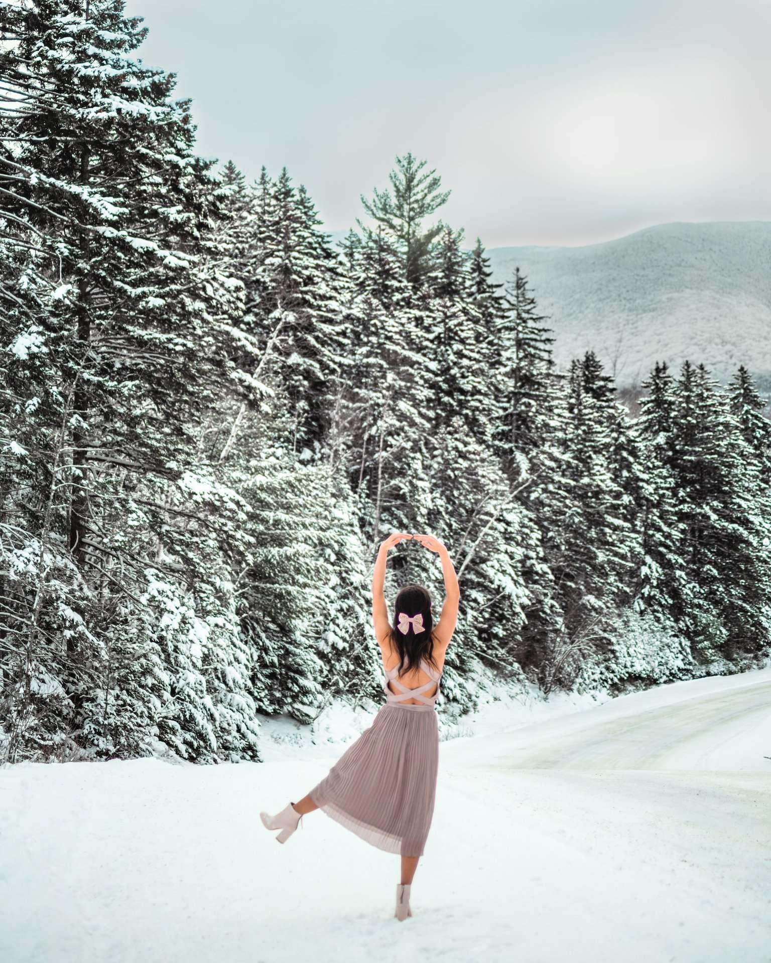 girl in dress dancing in snow from back