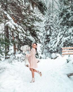 girl in snowy woods with oversized teddy bear