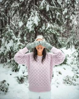 girl with mittens playing peek-a-boo in snow