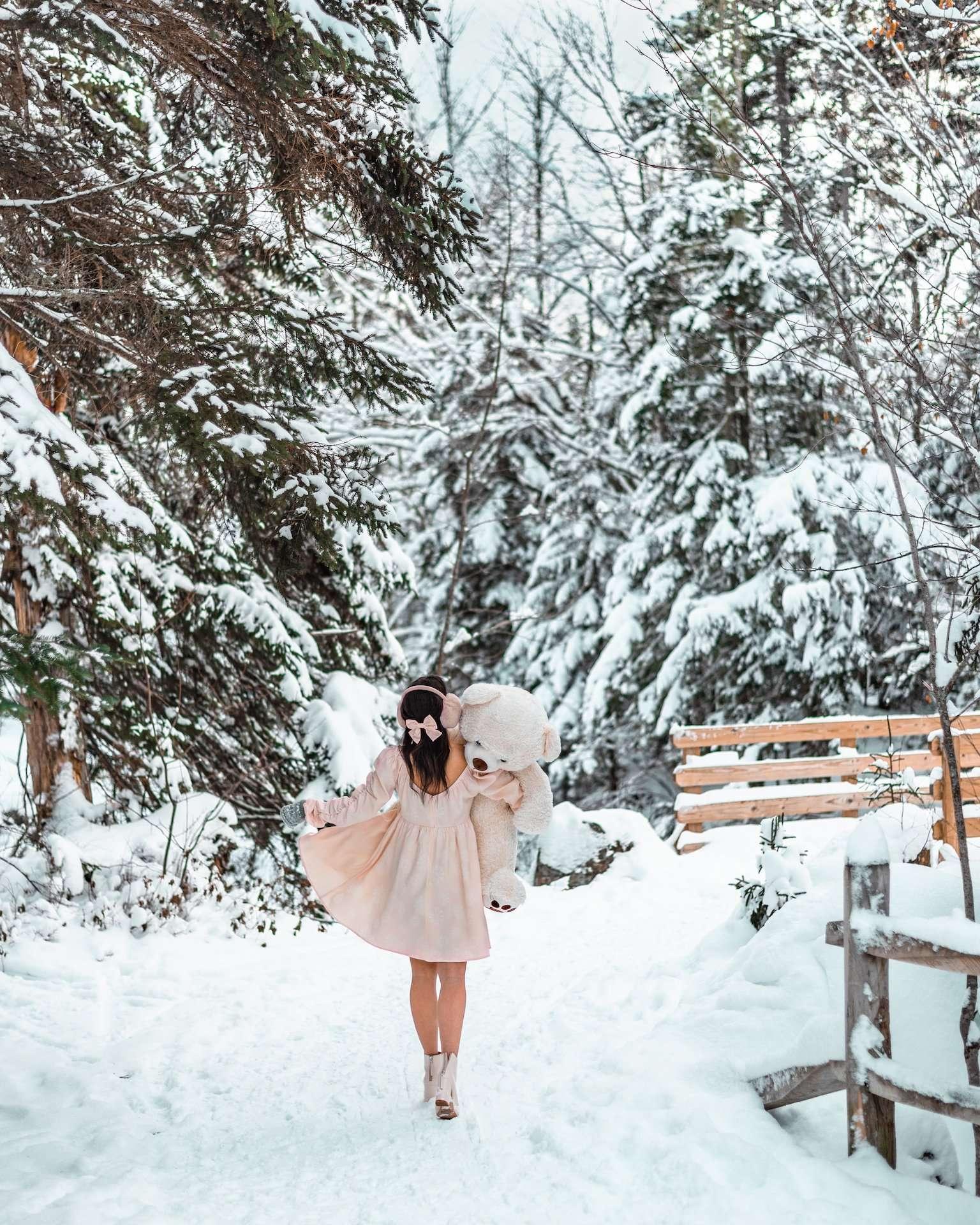 girl with oversized teddy bear in snowy woods
