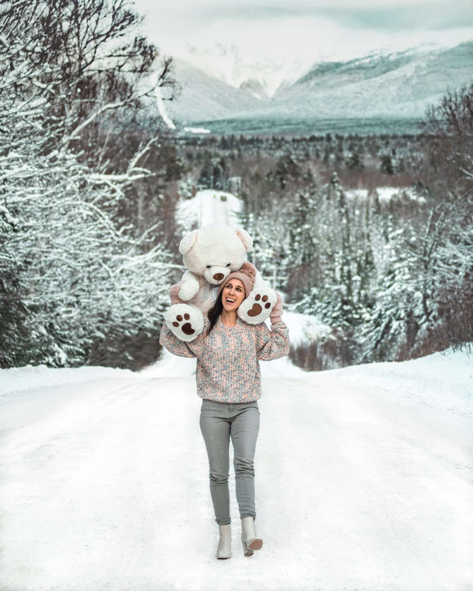 girl with oversized teddy bear on shoulders in snow
