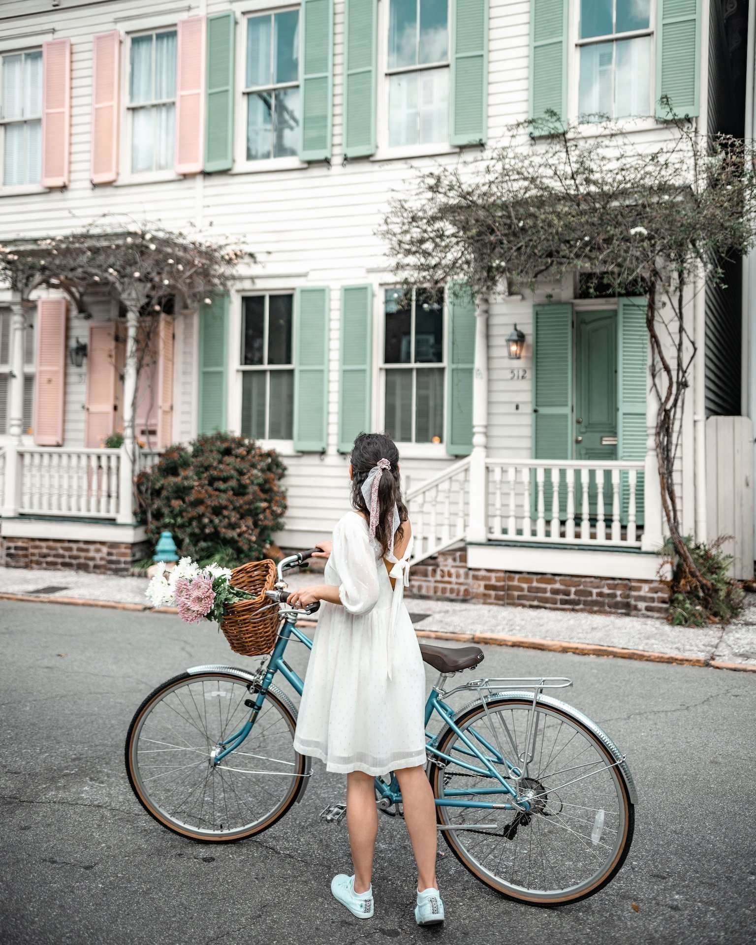 girl with bike in front of pastel home